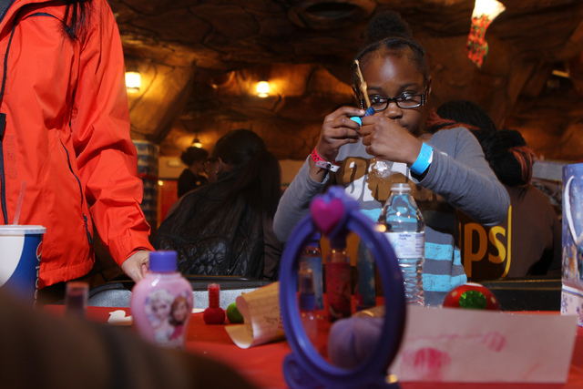 Aloyalty, 8, plays with her makeup after receiving it as a Christmas gift during an event hosted by St. Jude's Ranch for Children at Circus Circus Adventure Dome in Las Vegas Sunday, Dec. 14, 2014 ...