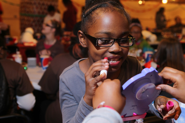Aloyalty, 8, uses her girl lipstick after receiving it as a Christmas gift during an event hosted by St. Jude's Ranch for Children at Circus Circus Adventure Dome in Las Vegas Sunday, Dec. 14, 201 ...