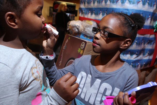 Aunesty, left, 8, gets lipstick from her twin sister Aloyalty, 8, after receiving girl makeup products as a Christmas gift during an event hosted by St. Jude's Ranch for Children at Circus Circus  ...