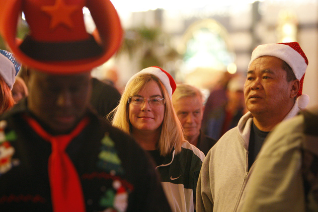 Cheryl Kinares, left, and her husband Kittisak, wait during the annual Fremont Street Experience's Christmas Tree Lighting event in Las Vegas Tuesday, Dec. 9, 2014. (Erik Verduzco/Las Vegas Review ...