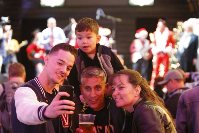 Jeremy Monterroso, from left, his son Liam, 4, on the shoulders on his father Luis, and mother Judy, take a photo together during the annual Fremont Street Experience's Christmas Tree Lighting eve ...
