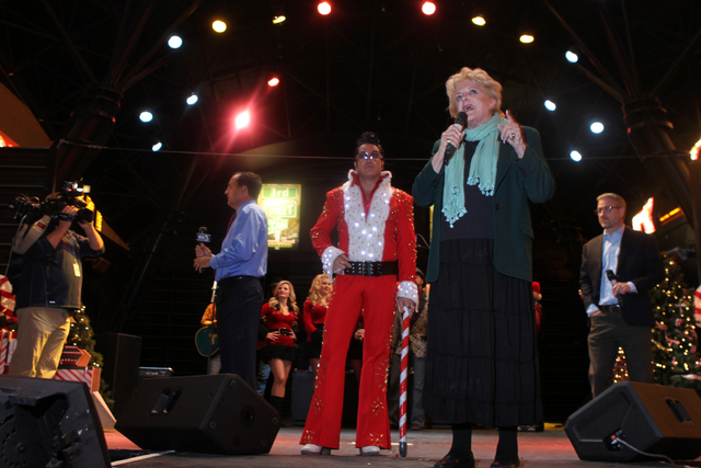 Jesse Garon, left, in costume as Santa Elvis, listens to Las Vegas Mayor Carolyn Goodman as they get ready for the Fremont Street Experience's Christmas Tree Lighting event in Las Vegas Tuesday, D ...