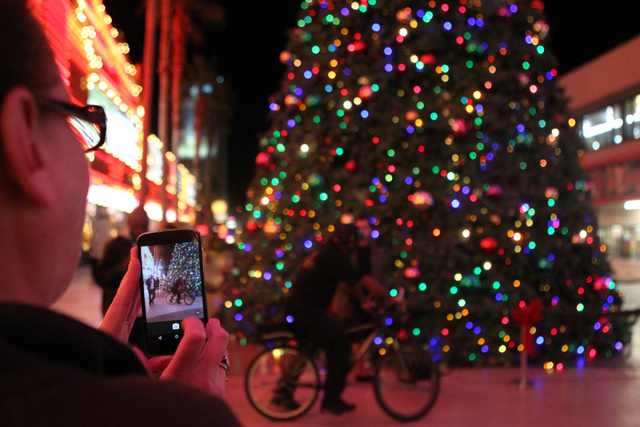 Mandy Backus takes a photo of the 50-foot Christmas tree during the annual Fremont Street Experience's Christmas Tree Lighting event in Las Vegas Tuesday, Dec. 9, 2014. (Erik Verduzco/Las Vegas Re ...
