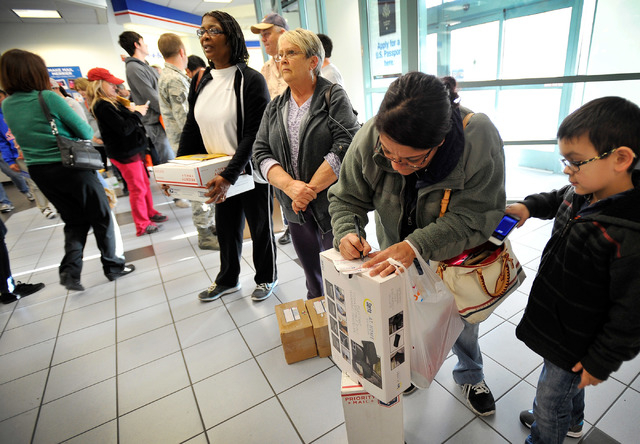 Michelle Allen, second right, addresses labels for holiday gifts to be shipped at the Crossroads branch of the U.S. Post Office on Monday, Dec. 15, 2014, in Las Vegas. Allen and her son, Brandon,  ...