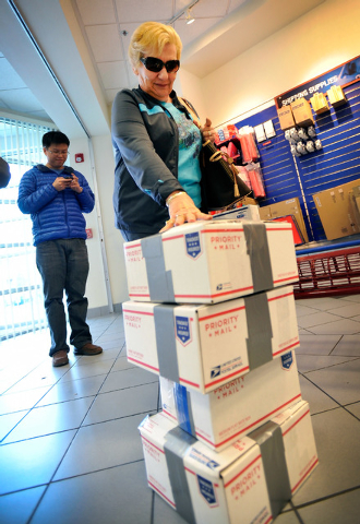 Bonnie Drefs steadies her stack of holiday gifts as she inches forward to the service counter at the Topaz branch of the U.S. Post Office on Monday, Dec. 15, 2014, in Las Vegas. Monday was the fin ...