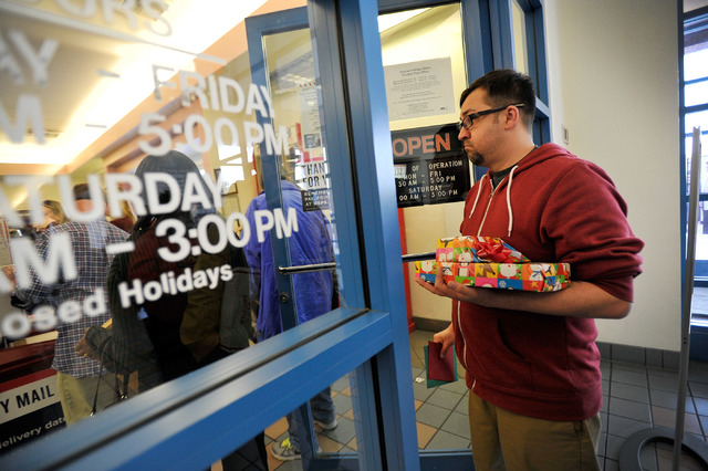 John Berry waits in line to mail his holiday gift at the Red Rock Vista branch of the U.S. Post Office on Monday, Dec. 15, 2014, in Las Vegas. Monday was the final day the post office to would gua ...