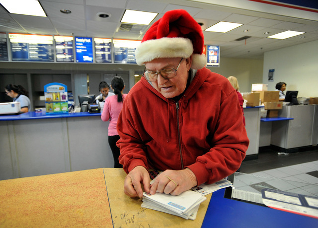 Bill Biel applies postage to his Christmas cards at the Crossroads branch of the U.S. Post Office on Monday, Dec. 15, 2014, in Las Vegas. Monday was the final day the post office to would guarante ...