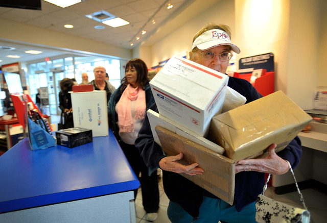 Barbara Butturini struggles to carry packages to counter at the Topaz branch of the U.S. Post Office on Monday, Dec. 15, 2014, in Las Vegas. Butturini got caught in the holiday rush as she volunte ...