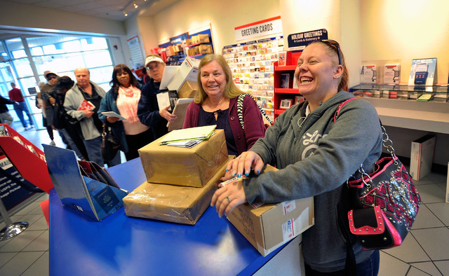 Elaine Panter, second right, and Christine Vaughan, right, share a laugh as they wait in line to mail-off their holiday gifts out of state family at the Topaz branch of the U.S. Post Office on Mon ...