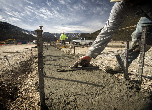 A man who did not want to be identified trowels concrete at the Spring Mountain Visitor Gateway on the Kyle Canyon Road approaching Mount Charleston,Tuesday, Feb. 18,2014. The gateway center will  ...