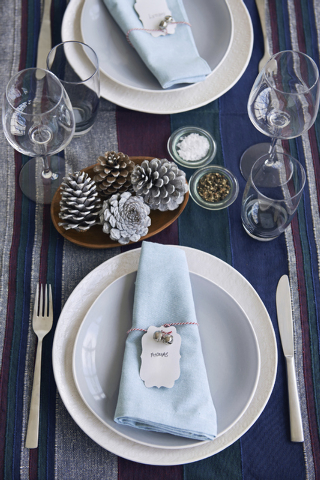 Thinkstock Frosted pine cones add a wintery touch to this simple place setting.