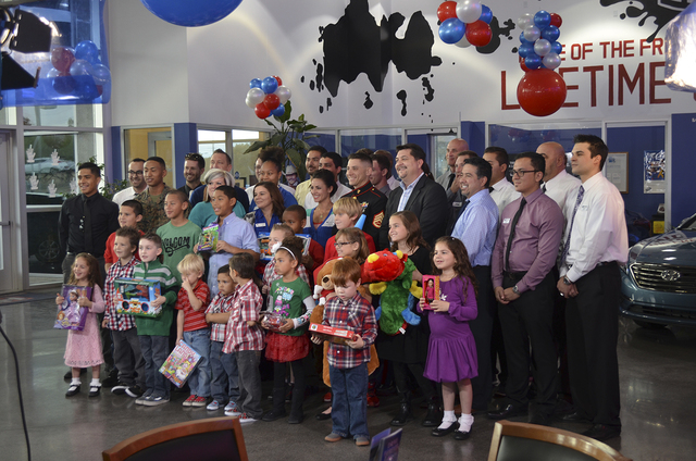 Courtesy photo Henderson Hyundai Superstore sales staff posses with Toys for Tots U.S Marine Corp Reserve representatives and participating children.