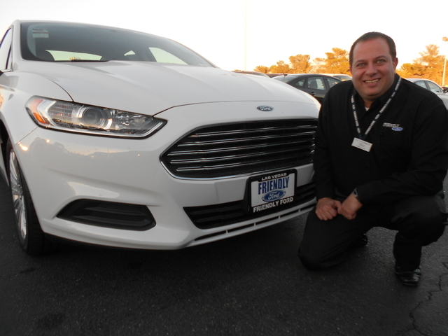 Courtesy photo Friendly Ford New Car Sales Manager Eli Columbus, who owns a 2013 Ford Fusion Energi, poses with a 2015 model at the dealership situated at 660 N. Decatur Blvd.