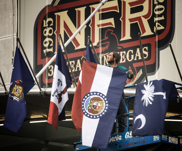 Dylan Shuaib places home-state flags of contestants competing in the Wrangler National Finals Rodeo in front of the Thomas & Mack Center on Monday, Dec. 01, 2014. This year's NFR, which opens Thur ...