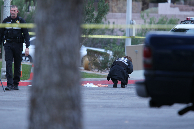 A Las Vegas police investigator photographs the scene of a reported shooting at the intersection of Tompkins Avenue and Tiburon South Avenue in Las Vegas Sunday, Dec. 21, 2014. (Erik Verduzco/Las  ...