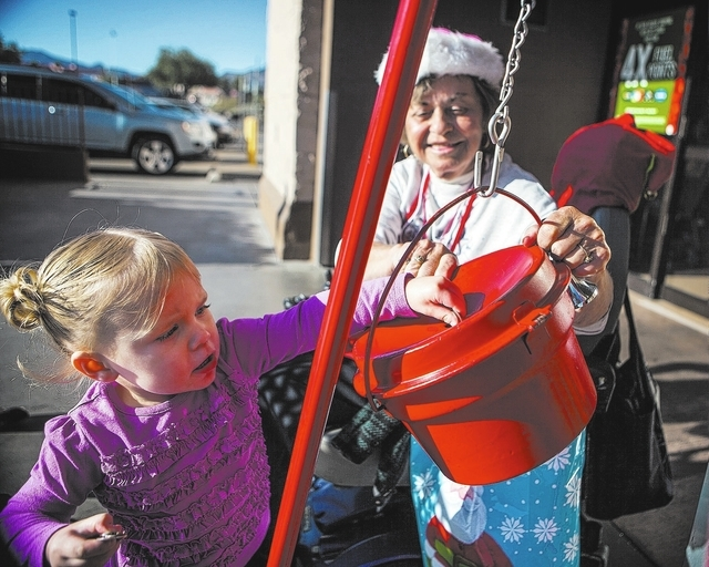 Salvation Army Henderson Corps bell ringer Patricia Adler, 73, tilts the bucket while Reese Hansen, 2, deposits money in front of Smith's Food & Drug Center in Henderson  on Tuesday, Dec. 9, 2014. ...