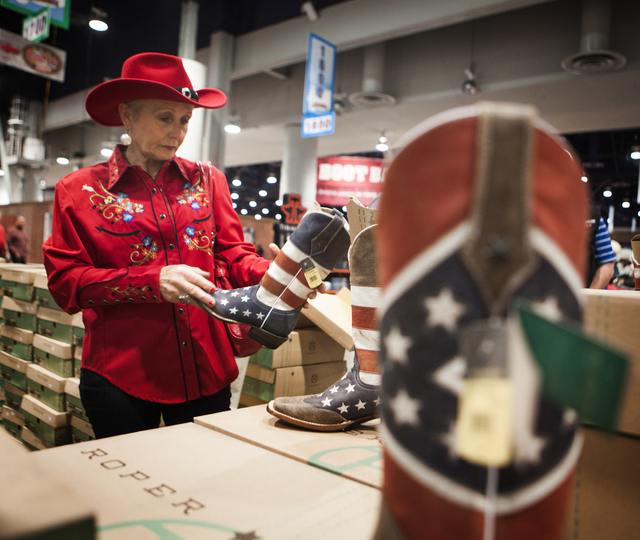Las Vegan Gundi Commins looks at a pair of Roper boots  at  Cowboy Christmas Gift show in the Las Vegas Convention Center on Tuesday, Dec. 9,2014.  Commons originally from Germany has been wearing ...