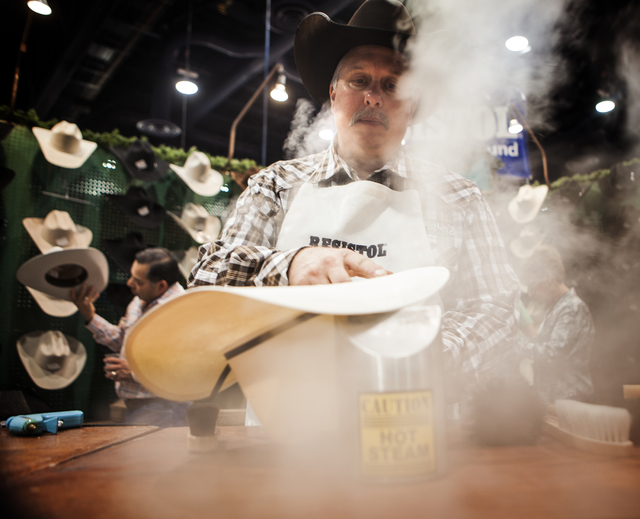 Jay Palm, owner of Jay Palm's Saddle Shop, steams a Resistol cowboy hat during the Cowboy Christmas Gift show in the Las Vegas Convention Center on Tuesday, Dec. 9,2014.  He said his independent w ...