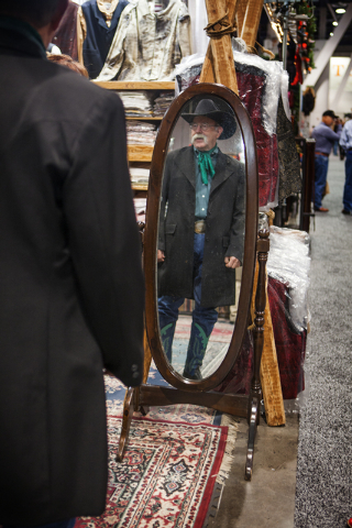 A reflection of Ted Taylor while he tries on a  frock in The Frontier Clothing Company booth on Tuesday, Dec. 9,2014 during the  Cowboy Christmas Gift show in the Las Vegas Convention Center.  The ...