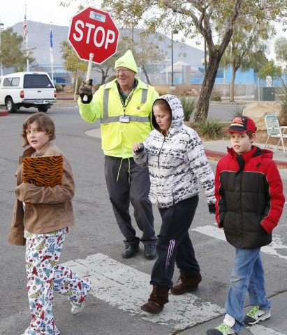 Jerry Enlow, 74, crossing guard, assists students across the street at the corner of Basic Road and Lead Street in Henderson, near McCaw Elementary School. Henderson is outsourcing crossing guards ...