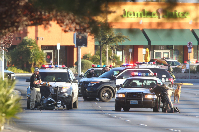 A suicidal man holds a gun to his head, seen left, as Las Vegas police have their guns drawn during a standoff on Decatur Boulevard near Charleston Boulevard in Las Vegas on Monday, Dec. 1, 2014.  ...