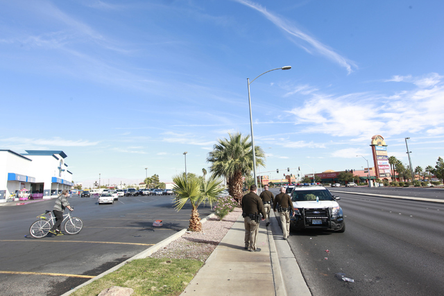 Las Vegas police walk around the scene where an armed suicidal man, who was detained, threatened to kill himself during a standoff on Decatur Boulevard near Charleston Boulevard in Las Vegas on Mo ...