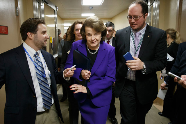 Senate Intelligence Committee Chair Sen. Dianne Feinstein, D-Calif., is pursued by reporters on Capitol Hill in Washington, Tuesday, Dec. 9, 2014, as she arrives to release a report on the CIA's h ...