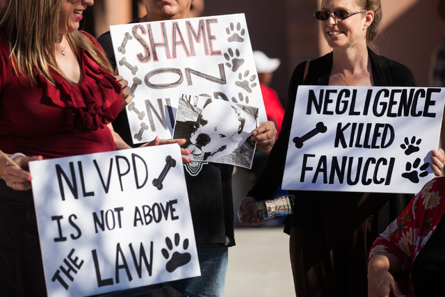 From left, Julie Monteiro, Trinidad Roman and Dawn Martinez hold up signs in support of Fanucci, a dog who died during a North Las Vegas police investigation at the home of Monteiro, during a rall ...