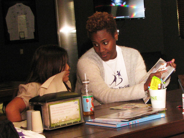 "Zappos staff member Temple Brathwaite and her ""Little"" Violeta read a book Nov. 13 inside the bistro at the company's offices, 400 E. Stewart Ave. Brathwaite volunteers once a week with Big  ..."