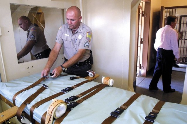 Senior Correction Officer Johnnie Hill adjusts a restraint in the execution chamber at the Nevada State Prison in Carson CIty, Nev., in this file photo from July 9, 2002.  Warden Mike Budge, rear, ...