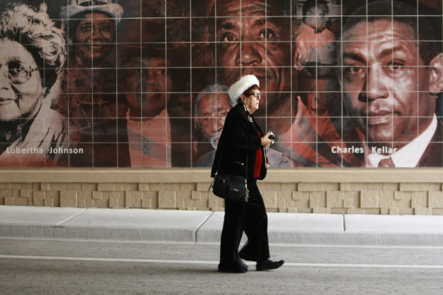 Georgette Dante walks past one of the several art murals depicting key national and local figures and places during the reopening ceremony of F Street near McWilliams Avenue and beneath Interstate ...