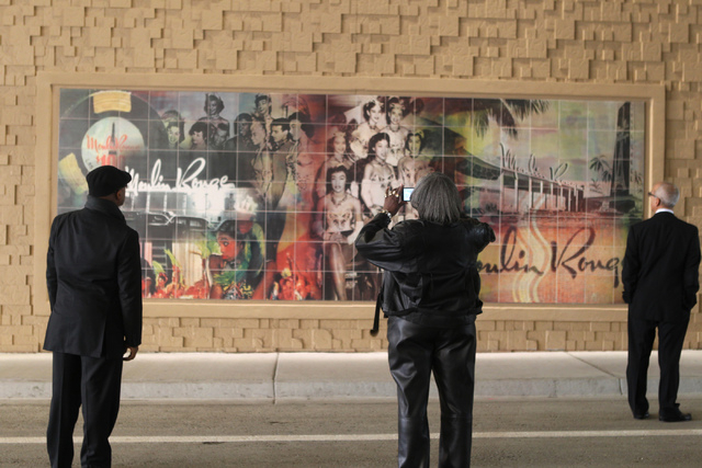 People stand in front of one of the several art murals depicting key national and local figures and places during the reopening ceremony of F Street near McWilliams Avenue and beneath Interstate 1 ...