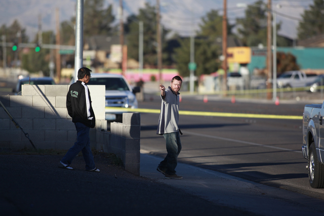 Area residents approach Las Vegas police officers during an investigation at the scene of a fatal vehicle-pedestrian crash on Lake Mead Boulevard at Linn Lane, east of Nellis Boulevard, in Las Veg ...
