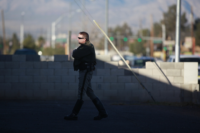 A Las Vegas police officer speaks with area residents during the investigation of a fatal vehicle-pedestrian crash on Lake Mead Boulevard at Linn Lane, east of Nellis Boulevard, in Las Vegas on Tu ...