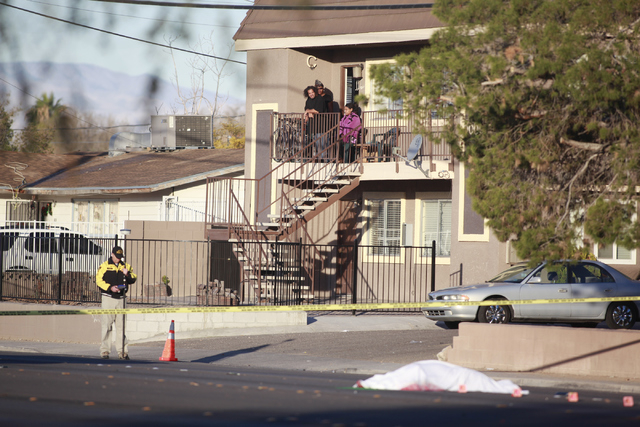 Area residents watch as Las Vegas police investigate the scene of a fatal vehicle-pedestrian crash on Lake Mead Boulevard at Linn Lane, east of Nellis Boulevard, in Las Vegas on Tuesday, Dec. 9, 2 ...