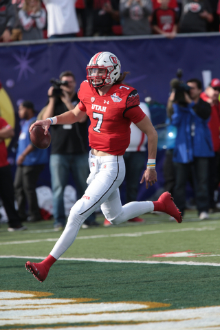 University of Utah's Travis Wilson (7)(QB) runs the ball in for a touchdown during the first half  of the  Royal Purple Las Vegas Bowl at Sam Boyd Stadium, Las Vegas, Saturday, Dec. 20, 2014. (Don ...