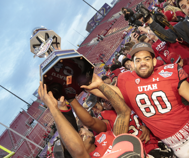 University of Utah's Westlee Tonga (80)(TE) helps hoist the winning trophy amongst a sea of supporters and team mates after the University of Utah won the bowl game with a score of 45-10 against C ...