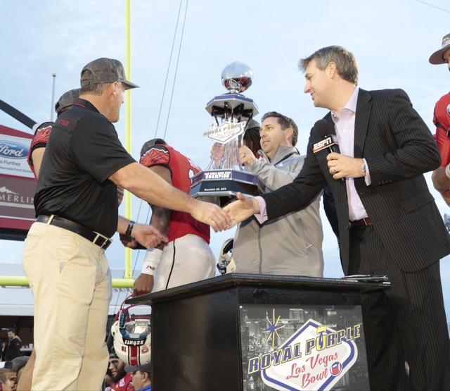 Kyle Whittingham - Head Coach -left, of the University of Utah football team, prepares to receive the winning trophy and shake the hand of Royal Purple President Bryan Yourdon -Right, after winnin ...