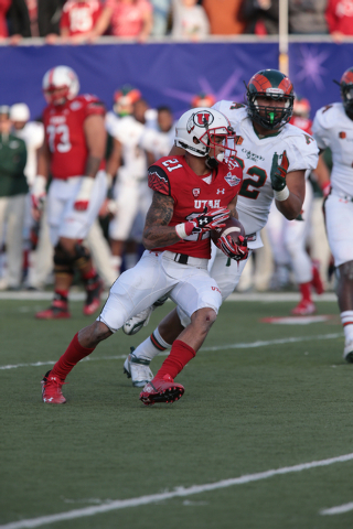 University of Utah's Troy McCormick (21)(RB) looks for an opening up field while trying to avoid Colorado State University's Josh Lovingood (92)(DL) who his close behind him during the second half ...