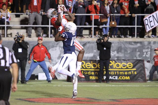 UNLV wide receiver Devante Davis pulls in a touchdown pass under coverage from Nevada defensive back Evan Favors during their game Saturday, Nov. 29, 2014 at Sam Boyd Stadium. (Sam Morris/Las Vega ...