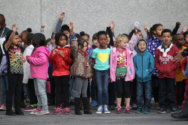 Children lineup to greet firefighters delivering toys to their school at Antonello Elementary School in North Las Vegas Thursday, Dec. 18, 2014. Multi agency firefighters and volunteers distribute ...