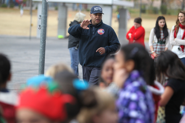North Las Vegas Firefighter Nino Galloway, vice president of the Firefighters of Southern Nevada Burn Foundation, talks to students during a toy delivery event to Antonello Elementary School in No ...