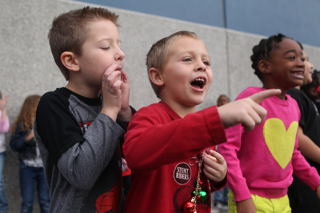 Brodie Keny, 5, from left, Tyler James, 5, and Zalaya Wiggins, react as fire engines arrive to their school to deliver toys at Antonello Elementary School in North Las Vegas Thursday, Dec. 18, 201 ...