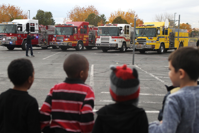 Fire engines line up at Antonello Elementary School in North Las Vegas Thursday, Dec. 18, 2014. Multi agency firefighters and volunteers distributed toys collected from the ҆ill the Fire Tru ...