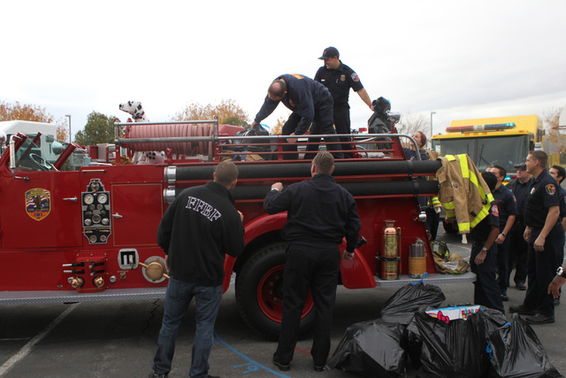 Multi agency firefighters unloads toys collected from the ҆ill the Fire TruckӠToy Drive to deliver to students at  Antonello Elementary School in North Las Vegas Thursday, Dec. 18, 201 ...