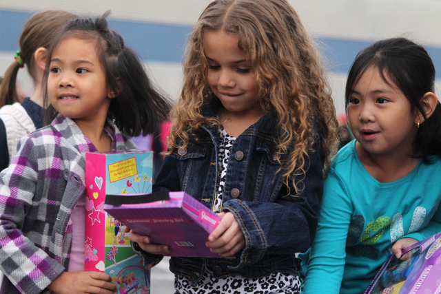Gabriela Romero, 5, from left, Emma Hardy, 5, and Alexxa Chan, hold toys they received from multi agency firefighters that were collected through the ҆ill the Fire TruckӠToy Drive at A ...