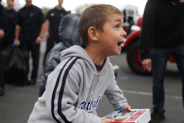 Christopher Mora, 6, reacts after receiving a gift from multi agency firefighters that were collected through the ҆ill the Fire TruckӠToy Drive at Antonello Elementary School in North  ...