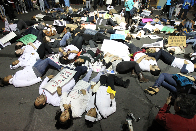 People protesting a officer-involved killings in which law enforcement received no punishment stage a die-in at Casino Center Drive and Charleston Boulevard during the First Friday art event in do ...