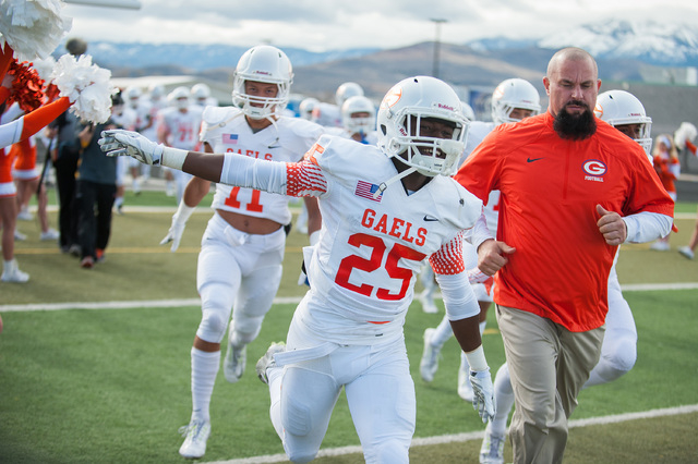 Bishop Gorman's Tyjon Lindsey (25) laughs while entering the field against Reed before the first half of the NIAA Nevada State High School Division I Championships game at Damonte Ranch High Schoo ...