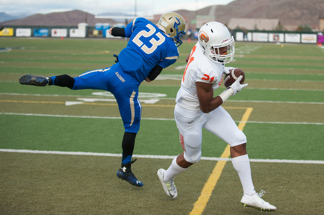 Bishop Gorman's Cordell Broadus (21) catches a touchdown pass against Reed's Porter Hansen (23) during the first half of the NIAA Nevada State High School Division I Championships game at Damonte  ...